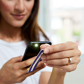 Brunette middle aged woman scanning test strip with mobile device flashlight